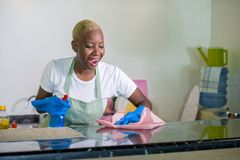 Young beautiful and happy African American black woman in washing rubber clothes cleaning home kitchen with cloth smiling cheerful. And positive in domestic stock photography