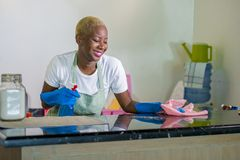 Young beautiful and happy afro American black woman in washing rubber clothes cleaning home kitchen with cloth smiling cheerful an. D positive in domestic stock photography