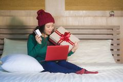 Young beautiful happy Asian American woman at home bed holding credit card and Christmas gift box shopping online xmas presents sm stock images
