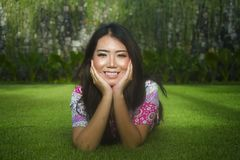 Young beautiful and happy Asian Chinese 20s woman lying relaxed. Smiling on green grass field feeling free and fresh enjoying and posing sweet in Summer Royalty Free Stock Photography