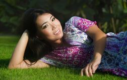 Young beautiful and happy Asian Chinese 20s woman lying relaxed. Smiling on green grass field feeling free and fresh enjoying and posing sweet in Summer Stock Photography