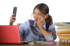 Young beautiful and happy Asian Chinese student girl studying with book pile and laptop computer desk taking selfie picture with stock photography