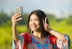 Young beautiful and happy Asian Chinese tourist woman on her 20s with colorful dress taking selfie pic with mobile phone camera on. Tropical green grass field Royalty Free Stock Photo