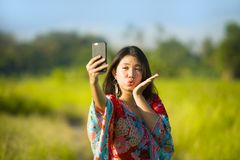 Young beautiful and happy Asian Chinese tourist woman on her 20s with colorful dress taking selfie pic with mobile phone camera on. Tropical green grass field Stock Image