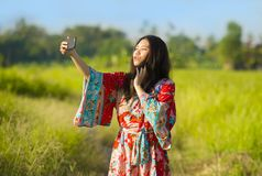 Young beautiful and happy Asian Chinese tourist woman on her 20s with colorful dress taking selfie pic with mobile phone camera on. Tropical green grass field Stock Photo