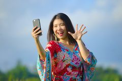 Young beautiful and happy Asian Chinese tourist woman on her 20s with colorful dress taking selfie pic with mobile phone camera on. Tropical green grass field Royalty Free Stock Photos