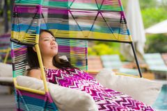 Young beautiful and happy Asian Chinese tourist woman relaxing at tropical luxury resort swimming pool sitting at hanging swing stock image