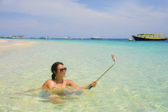 Young beautiful and happy Asian Chinese woman having fun on sea water taking selfie picture with mobile phone camera on paradise b Stock Photos