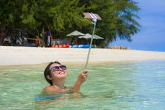 Young beautiful and happy Asian Chinese woman having fun on sea water taking selfie picture with mobile phone camera on paradise b Stock Image