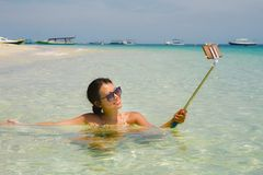Young beautiful and happy Asian Chinese woman having fun on sea water taking selfie picture with mobile phone camera on paradise b Stock Photography