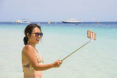 Young beautiful and happy Asian Chinese woman having fun on sea water taking selfie picture with mobile phone camera on paradise b Stock Photo