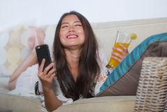 Young beautiful and happy Asian Chinese woman on her 20s or 30s lying at living room sofa couch drinking healthy orange juice usin. G internet mobile phone Royalty Free Stock Photos