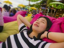 Young beautiful and happy Asian Chinese woman on her 20s or 30s smiling relaxed and cheerful lying on resort beanbag hammock royalty free stock photos