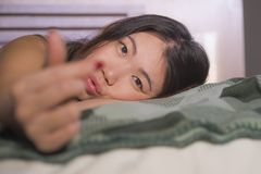 Young beautiful and happy Asian Chinese woman lying in bed at home bedroom smiling cheerful and relaxed posing sweet doing love si. Lifestyle portrait of young royalty free stock photography