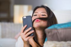Young beautiful and happy Asian Chinese woman lying at home sofa couch using internet dating app in mobile phone taking selfie por. Trait playing with her hair Royalty Free Stock Images