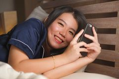 Young beautiful and happy Asian Chinese woman in pajamas using mobile phone social media texting with her boyfriend or enjoying stock images