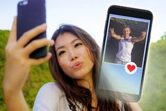 Young beautiful and happy Asian Chinese woman using internet online dating app on mobile phone sending like message to handsome Ca. Young beautiful and happy royalty free stock photo