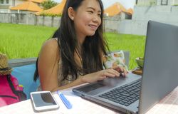 Young beautiful and happy Asian Chinese woman working outdoors with laptop computer networking green grass background cafe as digi stock image