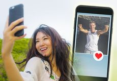 Young beautiful and happy Asian Chinese woman using internet online dating app on mobile phone sending like message to handsome Ca. Young beautiful and happy stock photo