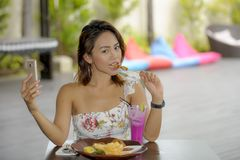 Happy Asian girl in sexy dress having brunch or lunch at holiday resort outdoors taking selfie pic with mobile phone Royalty Free Stock Photo