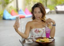 Happy Asian girl in sexy dress having brunch or lunch at holiday resort outdoors taking selfie pic with mobile phone Stock Photos