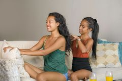 Young beautiful happy Asian girlfriends at home couch with one girl brushing the hair of the other woman helping preparing for dat royalty free stock images