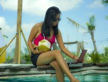 Young beautiful and happy Asian Indonesian teenager woman in bikini at tropical resort swimming pool networking relaxed and royalty free stock photo