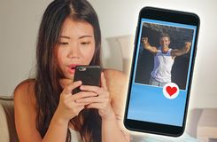 Young beautiful and happy Asian Korean girl using internet online dating app on mobile phone sending like message to handsome Cauc stock image