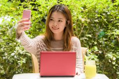Young beautiful and happy Asian Chinese student girl sitting at coffee shop garden working with laptop computer taking selfie stock photo