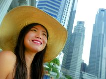Young beautiful and happy Asian Korean tourist woman in Summer hat luxury at hotel infinity pool enjoying city buildings view chee royalty free stock images