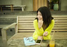 Young beautiful and happy Asian Korean woman sitting relaxed and happy at vintage wood coffee shop drinking orange juice reading royalty free stock image