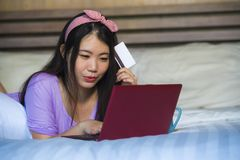Young beautiful happy Asian Korean woman using credit card internet banking on laptop computer at home in bed smiling shopping onl. Young beautiful and happy royalty free stock images