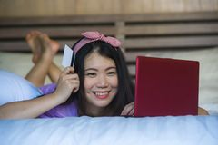 Young beautiful happy Asian Korean woman using credit card internet banking on laptop computer at home in bed smiling shopping onl. Young beautiful and happy royalty free stock photos