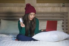 Young beautiful happy Asian Korean woman in winter hat relaxed on bed holding credit card using laptop computer for internet bank