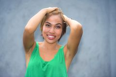 Young beautiful and happy Asian Singaporean or Malay woman smiling joyful with hands on her hair isolated on studio background. Head and shoulders portrait of Royalty Free Stock Images