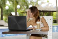 Beautiful happy woman in Summer dress outdoors at nice coffee shop having breakfast networking or working with laptop computer Stock Photos