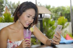 Happy Asian woman relaxed outdoors at coffee shop resort terrace with fruit juice using mobile phone texting and networking Royalty Free Stock Image