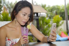 Happy Asian woman relaxed outdoors at coffee shop resort terrace with fruit juice using mobile phone texting and networking Stock Photography