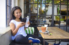 Beautiful happy Asian woman smiling relaxed enjoying breakfast using mobile phone Royalty Free Stock Photography