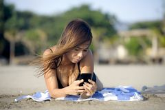 Beautiful and happy Asian woman using mobile phone texting on internet social media smiling relaxed Royalty Free Stock Images