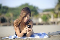 Beautiful and happy Asian woman using mobile phone texting on internet social media smiling relaxed Royalty Free Stock Image