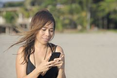 Beautiful and happy Asian woman using mobile phone texting on internet social media smiling relaxed Stock Photography