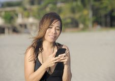 Beautiful and happy Asian woman using mobile phone texting on internet social media smiling relaxed Stock Photo
