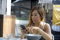 Beautiful and happy Asian woman using mobile phone texting on in Stock Photo