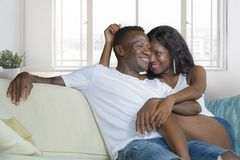Young beautiful and happy black African American couple in love relaxed at modern home living room cuddling sweet on sofa couch. Smiling having fun in royalty free stock photo