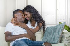 Young beautiful and happy black African American couple in love relaxed at modern home living room cuddling sweet on sofa couch royalty free stock photos