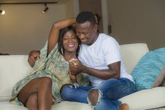 Young beautiful and happy black afro American couple in love relaxed at home living room sofa couch smiling cheerful having fun. Relaxed and cozy in successful stock photos