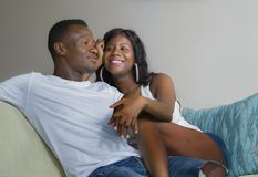 Young beautiful and happy black afro American couple in love relaxed at home living room sofa couch smiling cheerful having fun. Relaxed and cozy in successful royalty free stock photos