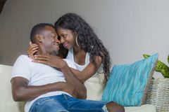 Young beautiful and happy black afro American couple in love relaxed at home living room sofa couch smiling cheerful having fun. Relaxed and cozy in successful royalty free stock images
