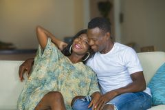 Young beautiful and happy black afro American couple in love relaxed at home living room sofa couch smiling cheerful having fun. Relaxed and cozy in successful stock photo